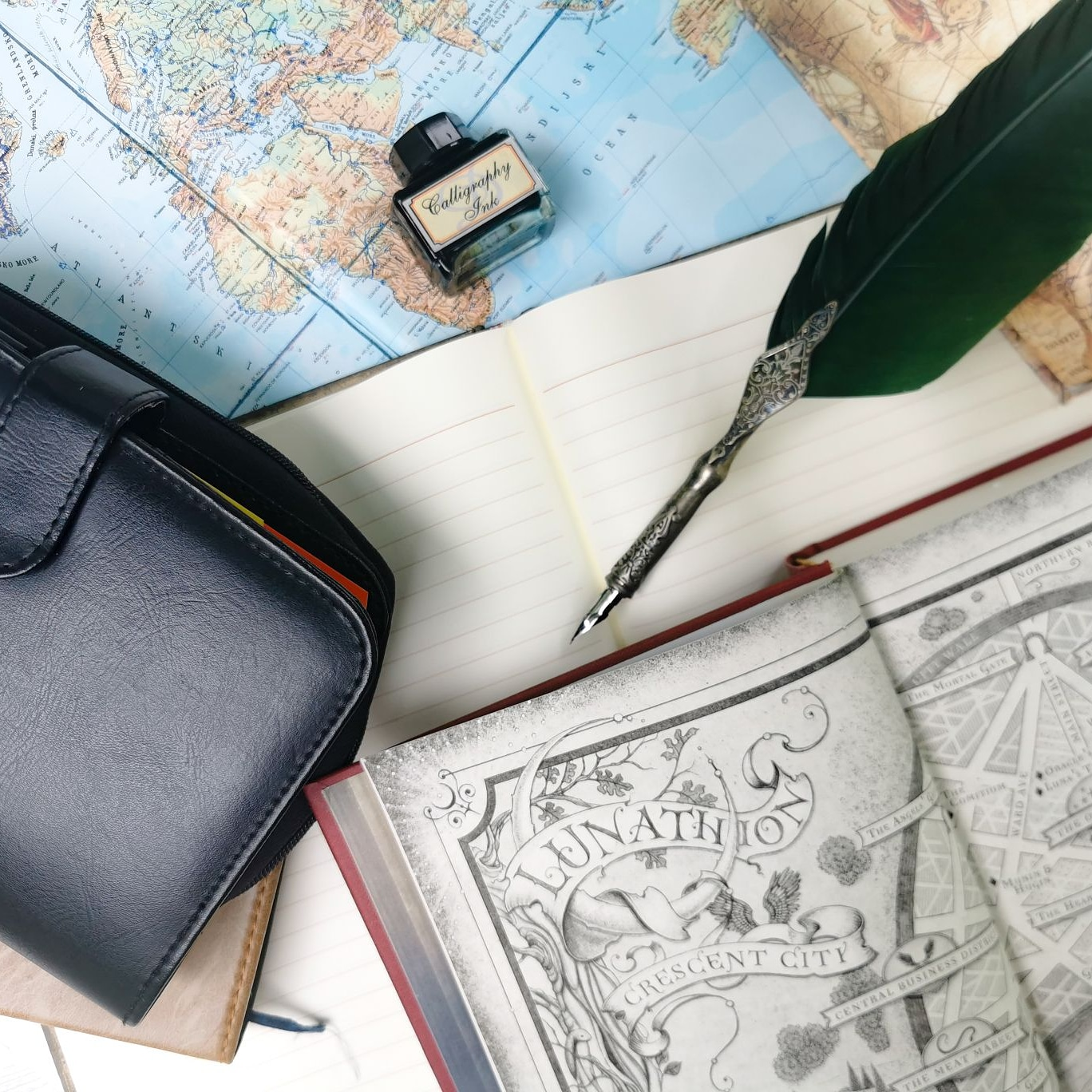 Map, book, notebooks and a quill